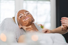 Woman getting chocolate mask treatment in spa. Beautician applying refreshing chocolate mask at young woman`s face Stock Photo