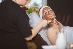 Woman getting chocolate mask treatment in spa. Beautician applying refreshing chocolate mask at young woman`s face Royalty Free Stock Photos