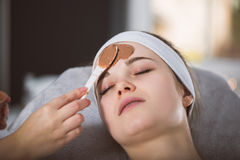 Woman getting chocolate mask treatment in spa. Beautician applying refreshing chocolate mask at young woman`s face Royalty Free Stock Image