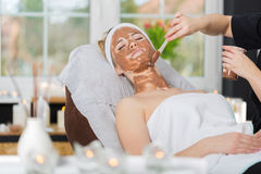 Woman getting chocolate mask treatment in spa. Beautician applying refreshing chocolate mask at young woman`s face Royalty Free Stock Photo
