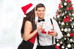 Woman getting a Christmas present from boyfriend Royalty Free Stock Images