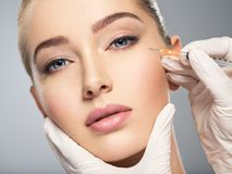 Woman getting cosmetic injection of botox in cheek royalty free stock photography