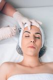 Woman getting cosmetic injection in her face on Royalty Free Stock Images