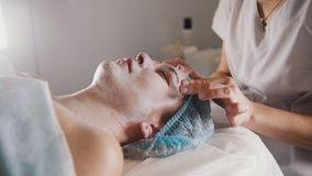 Woman getting a cosmetic procedure - mask facial massage at spa salon skincare stock images