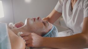 Woman getting a cosmetic procedure - mask facial massage at spa salon skincare. Close up stock footage