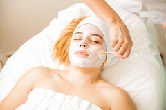 Woman getting a cream mask at the spa Stock Photos