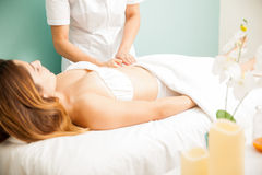Woman getting deep tissue massage. Profile view of a young brunette getting a deep tissue massage at a health and beauty spa Stock Images