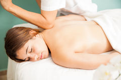 Woman getting a deep tissue  massage. Relaxed young women getting a deep tissue massage by a female therapist at a health clinic, seen up close Stock Photos