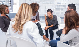 Woman getting depressed in group therapy. Woman sitting on chair and getting depressed in group therapy stock images