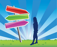 Woman getting directions. An illustrated view of a silhouetted woman standing in a large open field, looking at a directional sign with large colored arrows Stock Photo