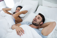 Woman getting disturbed with man snoring on bed. In bedroom Royalty Free Stock Photo