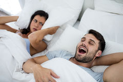 Woman getting disturbed with man snoring on bed Stock Image