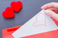 Woman getting from envelope paper sheet with pictured heart Royalty Free Stock Image