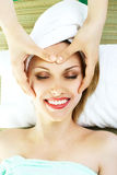 Woman getting a face massage. Beautiful happy young woman getting a professional face massage Royalty Free Stock Photos