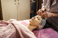 Woman getting facial care peeling mask by beautician at spa salo stock images