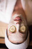 Woman is getting facial clay mask at spa stock photography