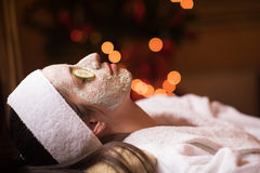 Woman is getting facial clay mask at spa stock images