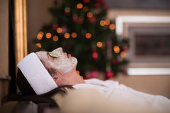 Woman is getting facial clay mask at spa stock image