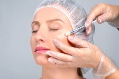 Woman is getting filler injection in cheeks. Anti-aging treatment and face lift. Cosmetic Treatment and Plastic Surgery. Woman is getting filler injection in royalty free stock image