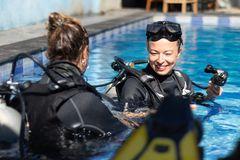 Woman getting first experience with scuba diving under the guidance of experienced recreational diving instructor in. Female diving instructor teaches student to royalty free stock photo