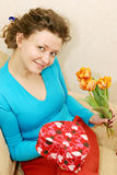 Woman getting flowers and gift Royalty Free Stock Images
