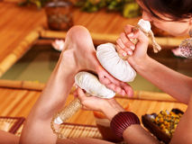 Woman getting foot massage in bamboo spa. Young woman getting foot massage in bamboo spa Royalty Free Stock Photography