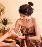 Woman getting foot massage in bamboo spa. Young woman getting foot massage in bamboo spa Royalty Free Stock Images