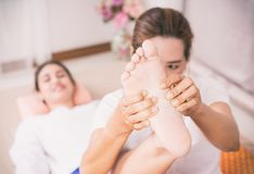 Woman is getting Foot massage reflexology, focusing on the Foot and hand. Woman is getting Thai Foot massage reflexology, focusing on the Foot and hand royalty free stock image
