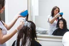 Woman getting hair colored in beauty salon Stock Photo