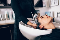 Woman getting hair wash done at salon. Closeup of hairdresser giving hair wash service to a customer at the salon. Woman getting hair spa treatment done at hair stock photo