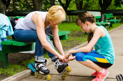 Woman getting help putting on rollerblades. Woman getting help from young girl putting on rollerblades Stock Images