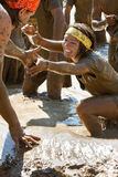 Woman getting help up out of a mud pit Royalty Free Stock Image