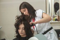 Woman getting her hairstyle done at hairdresser Stock Photo