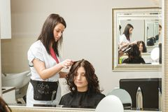 Woman getting her hairstyle done at hairdresser Stock Photos