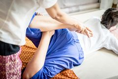 Woman getting her leg stretched in Thai Spa massage. Woman is getting her leg stretched in Thai Spa massage Stock Photos
