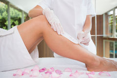 Woman getting her legs waxed by beauty therapist Stock Photos