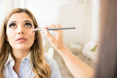 Woman getting her makeup done. Point of view of a makeup artist putting some makeup on a female customer in a beauty salon Royalty Free Stock Photos