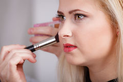 Woman getting her makeup done with professional brush Stock Image