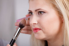 Woman getting her makeup done with professional brush Royalty Free Stock Image