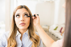 Woman getting her makeup done. Wide view of a makeup artist putting adding some mascara on a woman`s lower eyelashes in a beauty studio Royalty Free Stock Photography