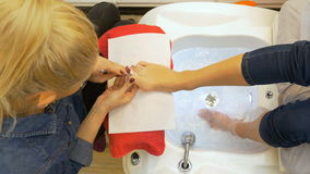 Woman getting her pedicure done by specialist at beauty salon stock video