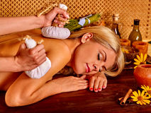 Woman getting herbal ball massage treatments . Royalty Free Stock Photography