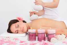 Woman getting herbal compress ball therapy Stock Image