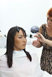 Woman getting herself a new hair style at beauty salon Stock Image