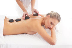A woman getting hot stone back massage on a white background Royalty Free Stock Image