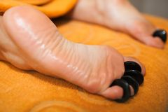 Woman getting hot stone massage on feet. Close-up shot of female feet under hot stone massage. Procedure at beauty spa salon Stock Photos