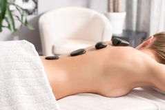 Woman getting hot stone massage in spa salon. Beauty treatments. Woman having a hot stone treatment and massage at spa Royalty Free Stock Photo