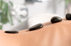 Woman getting hot stone massage in spa salon. Beauty treatments. Woman having a hot stone treatment and massage at spa Royalty Free Stock Photography