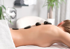 Woman getting hot stone massage in spa salon. Beauty treatments. Woman having a hot stone treatment and massage at spa Stock Photography
