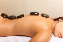 Woman getting a hot stone massage in spa salon Stock Images